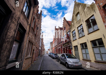 Typical old narrow paved street with traditional brick houses in Bruges, Belgium. - Stock Photo