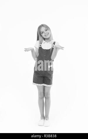 Girl in hot pink jumpsuit isolated on white background. Smiling kid wearing summer outfit. Child with hands in I don't know gesture. Blond girl with lovely face in studio, happy childhood concept. - Stock Photo