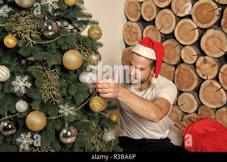 Man in santa claus hat decorate Christmas tree with balls, snowflakes, garlands on wood logs background. xmas, new year, eve, holidays celebration. Festive decorations and ornaments - Stock Photo