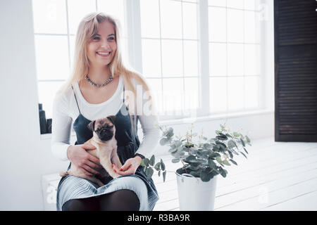 Attractive young girl with cute pug dog on the hands - Stock Photo
