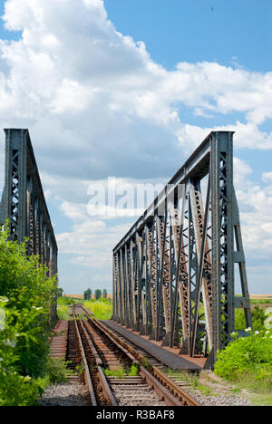 Old rusty railway bridge in the countryside - Stock Photo