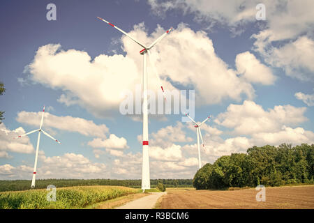 Wind farm in Lower Saxony, Germany. Turbines on field on cloudy blue sky. Global warming, climate change. Alternative energy source. Eco power, green technology concept. - Stock Photo