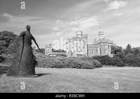 Wicker woman statue and castle in Stornoway, United Kingdom. Willow sculpture on green grounds of Lews Castle estate. Architecture and design. Landmark and attraction. Summer vacation and wanderlust. - Stock Photo