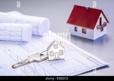 Blueprints and house as a keychain with architectural model   usage worldwide - Stock Photo