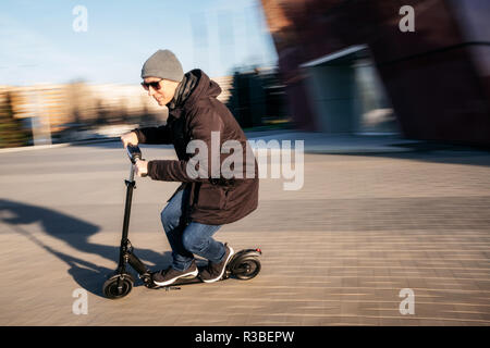 Young man in casual wear on electric kick scooter on city street in motion blur in autumn - Stock Photo