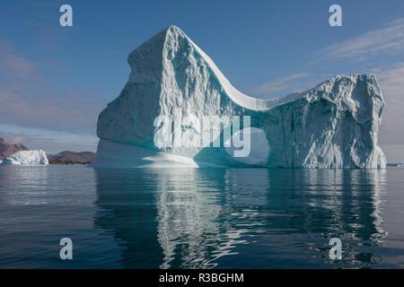 Eastern Greenland, Scoresbysund, aka Scoresby Sund, Bear Island, aka Bjorne Oer. Huge iceberg with hole around the Bear Islands. - Stock Photo