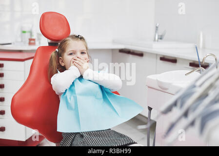 Frightened little girl at dentist office covered mouth with hands - Stock Photo