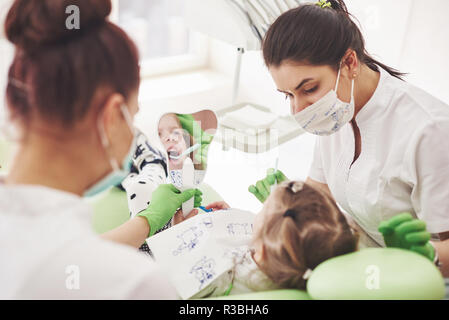 Hands of unrecognizable pediatric dentist and assistant making examination procedure for smiling cute little girl sitting on chair in hospital - Stock Photo