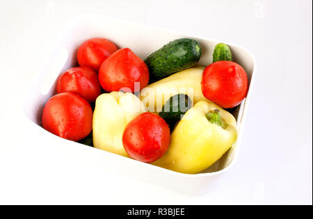 White bowl with assorted fresh vegetables on white background - Stock Photo