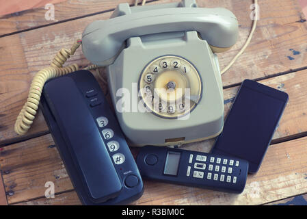 Different types of telephones landline phone, smartphone, phone with rotary on wooden board - Stock Photo