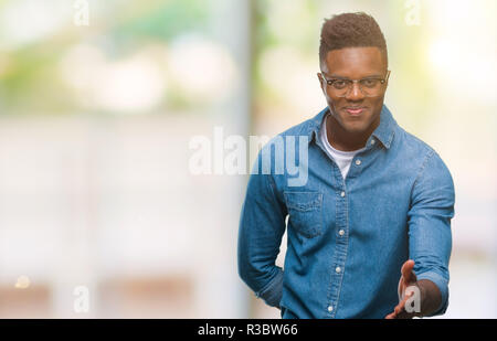 Young african american man over isolated background smiling friendly offering handshake as greeting and welcoming. Successful business. - Stock Photo