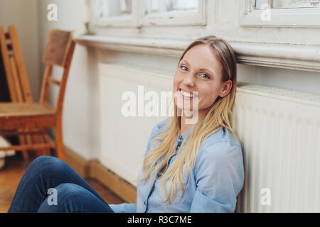 Happy friendly woman relaxing in the warmth as she leans against a radiator while sitting on the floor at home - Stock Photo