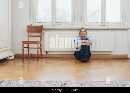 Lonely young woman sitting on the floor leaning against a warm radiator in a minimalist apartment - Stock Photo
