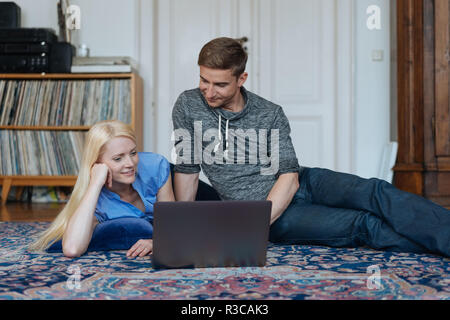 Young couple relaxing together on the carpet in the living room with a laptop computer smiling as they read something on the screen - Stock Photo