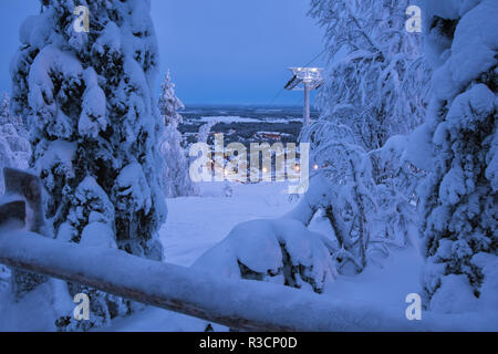 Winter wonderland evening landscape view on Levi ski resort in Laplandia, Finland, with ski lift, village and trees covered by snow. Seasonal winter g - Stock Photo