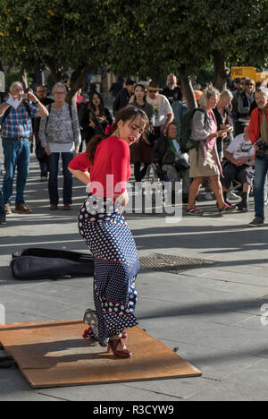 A young woman flamenco dancer performs for tourists on a street in Seville, Andalucia, Spain - Stock Photo