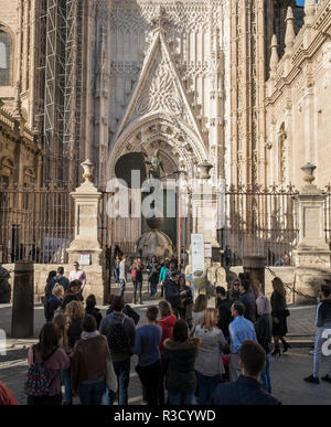 Tourists outside the entrance of Seville Cathedral, a UNESCO World Heritage Site, admiring restoration work on the decorative exterior facade. Spain. - Stock Photo