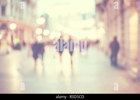 abstract blur people background, silhouettes of unrecognizable people walking on a street in winter evening with bokeh lights - Stock Photo