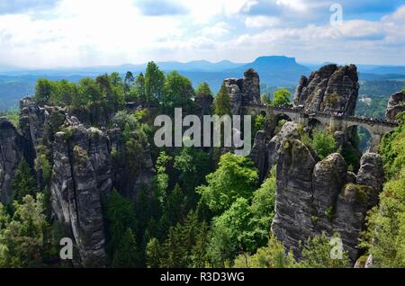 The mountain range Elbe Sandstone Mountains (Elbsandsteingebirge) near the town of Rathen in Saxony in Germany, people crossing the old bastion bridge - Stock Photo