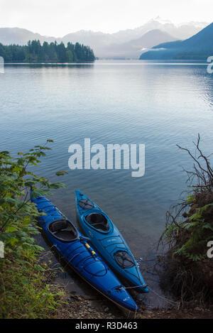 USA, WA. Kayaks tied at shore Anderson Point Campground. Mt. Shuksan morning light - Stock Photo