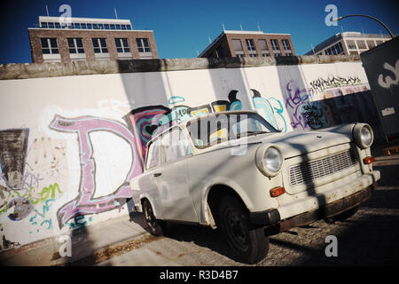 Berlin Germany - Trabant car parked alongside the Berlin Wall at the East Side Gallery - 2018 - Stock Photo