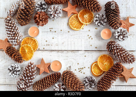 Christmas mood background with pine cones, dried orange slices, candles and star sprinkles - Stock Photo
