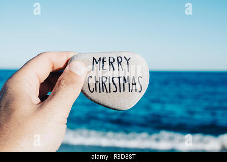 closeup of a young man with a stone in his hand, with the text merry christmas handwritten in it, on the beach, with the ocean in the background - Stock Photo