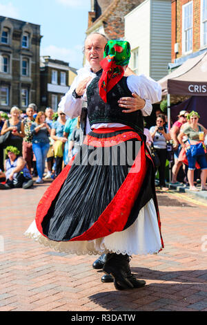 Faversham Hop Festival 2018, senior Hungarian man and woman in traditional costume dancing waltz style in front of audience in town street. - Stock Photo