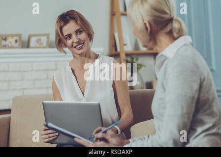 Assistance. Delighted elderly woman sitting on the couch and writing notes in notebook while having pleasant conversation with cheerful social worker - Stock Photo