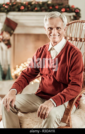 Happy free time. Senior joyful intelligent man sitting on the chair looking straight and smiling. - Stock Photo