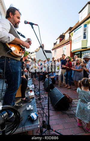 'Apples I'm home' pop folk band performing on small street stage at the Faversham Hop Festival. Side view of band and audience in town street. - Stock Photo