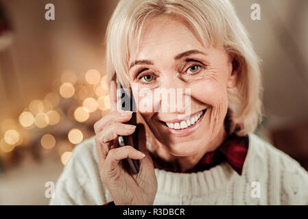 Best connection. Pleasant elderly occupied woman being in the bright room smiling and having conversation. - Stock Photo