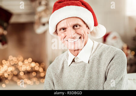 Be happy. Joyful pleasant elderly man being in the bright room looking straight and smiling. - Stock Photo