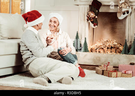 Common celebration. Satisfied elderly happy couple sitting on the floor near the fireplace smiling and holding glasses of champagne. - Stock Photo