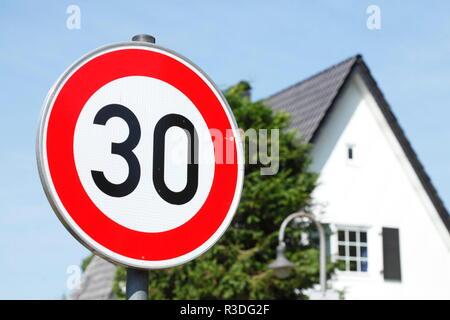 Road sign Tempo 30 Zone, one-family house in the background, Germany, Europe  I Verkehrsschild Tempo 30 Zone, Einfamilienhaus im Hintergrund , Deutsch - Stock Photo