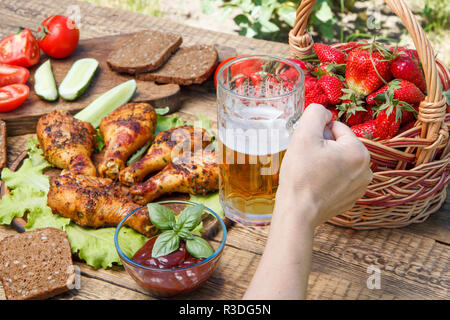 Female hand is holding glass mug of beer with grilled chicken legs and tomatoes, cucumber, black dread, wicker basket with strawberries on the backgro - Stock Photo