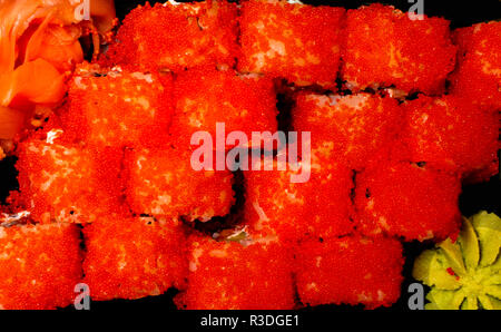California beautiful fresh sushi with tobiko caviar, red caviar, on a plate, isolated on a black background, close-up, traditional Japanese cuisine - Stock Photo