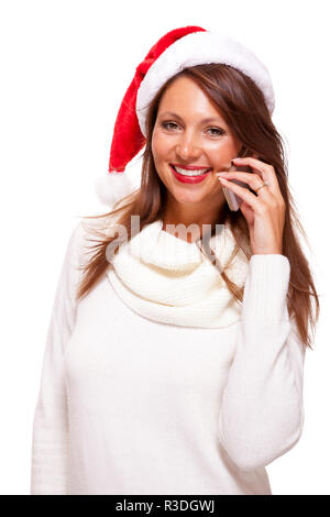 attractive woman with red santa claus hat reads a text message on her mobile phone and sent christmas wishes - Stock Photo