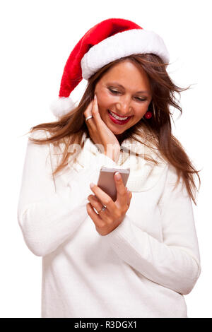 attractive woman with red santa hat reading a text message on her mobile phone and sent christmas wishes - Stock Photo