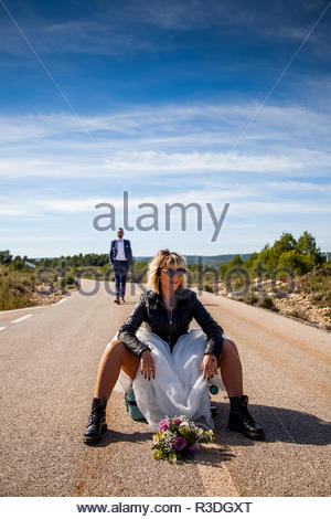 Rocker bride with black leather jacket, boots and sunglasses sitting on a suitcase in the middle of a lonely road and her groom poses behind her. - Stock Photo