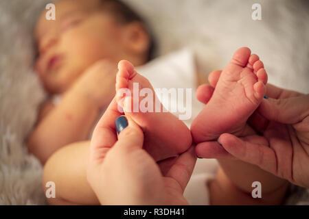 Beautiful infant baby feet in mother hands. feet of little baby boy, newborn baby foot, newborn baby finger, - Stock Photo