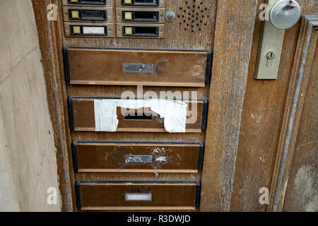 old destroyed doorbells at a wooden door with letter box - Stock Photo