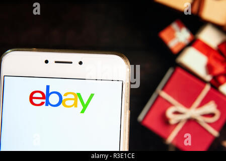 American multinational e-commerce  online auction and shopping company Ebay logo is seen on an Android mobile device with a Christmas wrapped gifts in the background. - Stock Photo
