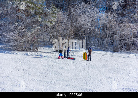 Adygea, Russia - January 23,  2017: Young couple with children riding on an inflatable sledding tubing on a snowy slope on a winter day - Stock Photo