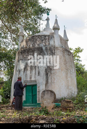 Harari man praying in front of an old muslim grave, Harari Region, Harar, Ethiopia - Stock Photo