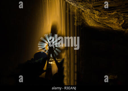 Night photograph inside a cave with waterfall and illuminated with coloured lanterns to highlight the figure of the model. - Stock Photo