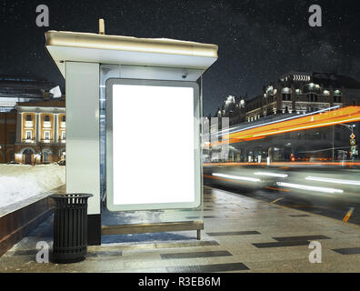 Bus stop at city night with blank white illuminated poster. - Stock Photo