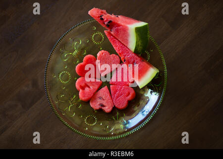 Healthy watermelon smoothie with mint, a piece of watermelon, hearts and a striped straw on a wood background - Stock Photo