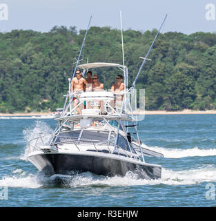 people on a power boat with Shelter Island in the background - Stock Photo