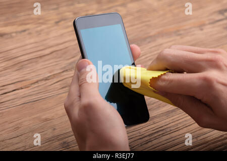 Man Cleaning Mobile Phone Screen With Yellow Cloth Over Wooden Desk - Stock Photo